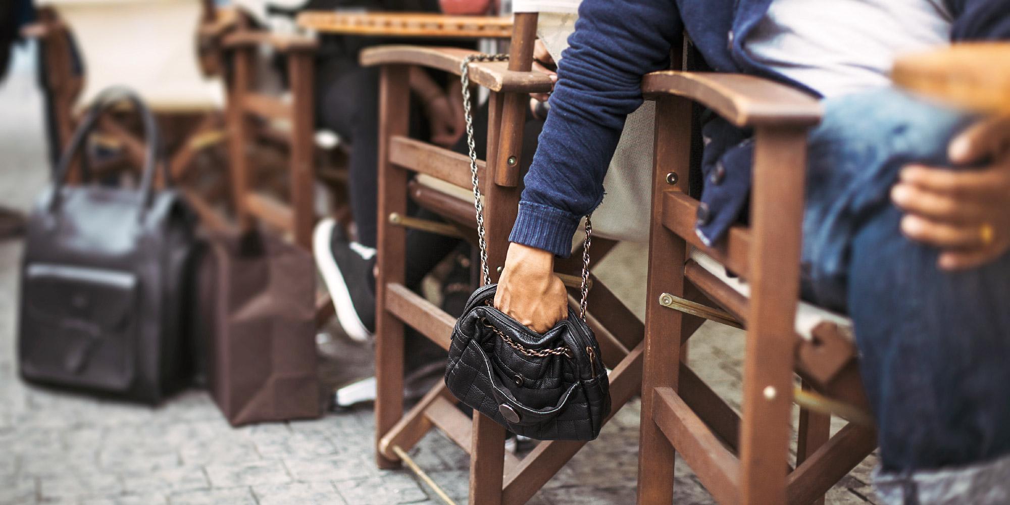 En person stjäl plånbok ur handväska.